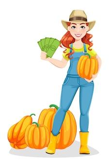 Bela mulher agricultora em pé perto de abóboras e segurando dinheiro.