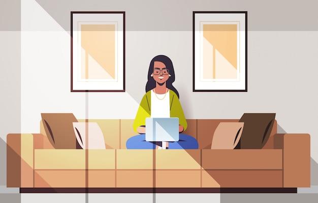 Bela mulher indiana sentada no sofá, usando a garota do laptop trabalhando em casa freelance conceito moderna sala interior horizontal comprimento total