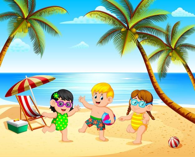 Bela vista com três crianças brincando na praia sob o céu azul