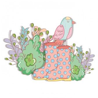 Belo pássaro com botas de jardinagem e bush