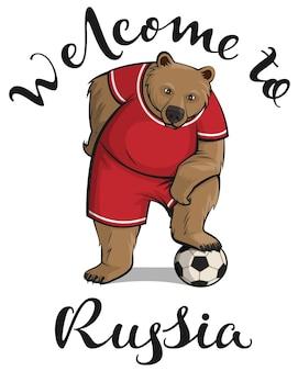Bem-vindo ao texto da rússia e o jogador do urso pisou na bola de futebol isolada