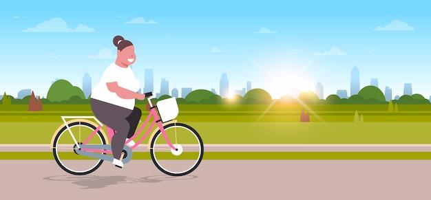 Bicicleta de equitação mulher no parque urbano da cidade menina ciclismo bicicleta conceito de perda de peso