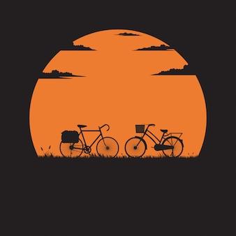 Bicicleta de silhueta dois no prado com o pôr do sol para o fundo
