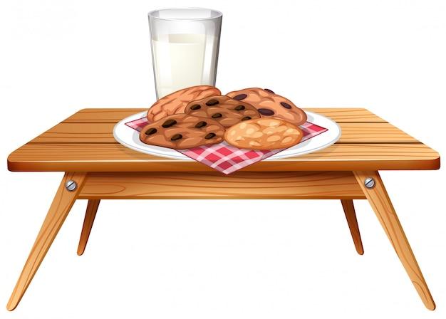 Biscoitos de chocolate e leite na mesa de madeira