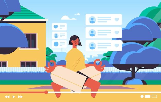 Blogueira de fitness feminino gravação de blog de vídeo online streaming ao vivo blogging vlog popularidade conceito vlogger mulher sentada pose de lótus no quintal horizontal