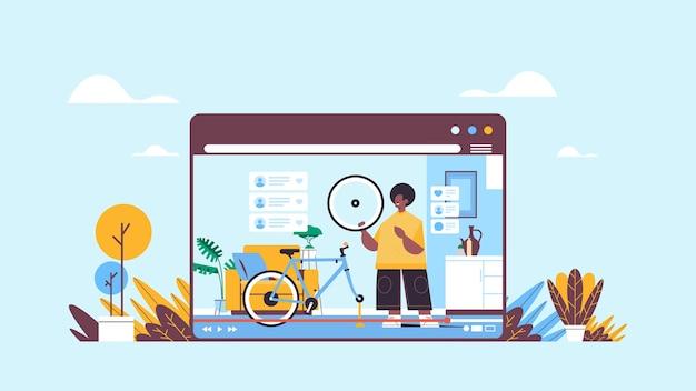 Blogueiro masculino consertando bicicleta gravação de vídeo blog online streaming ao vivo conceito de blogging homem verificando defeitos nos pneus oficina interior janela do navegador da web horizontal