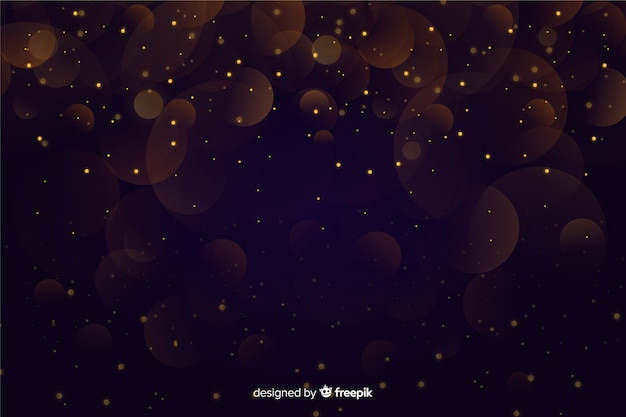 Bokeh de partículas douradas sobre fundo escuro