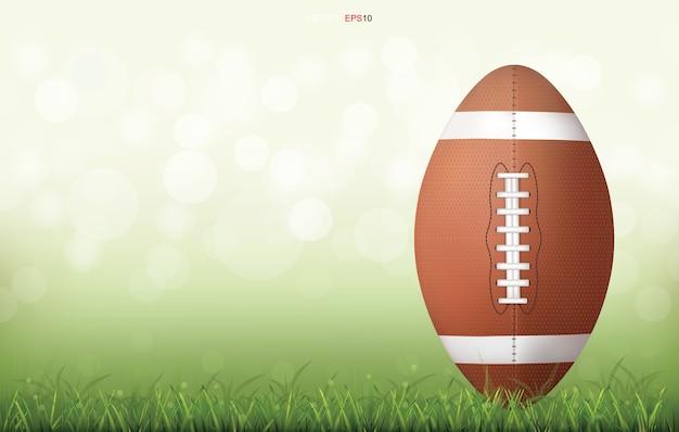 Bola de futebol americano em campo de grama verde com fundo de bokeh luz desfocada