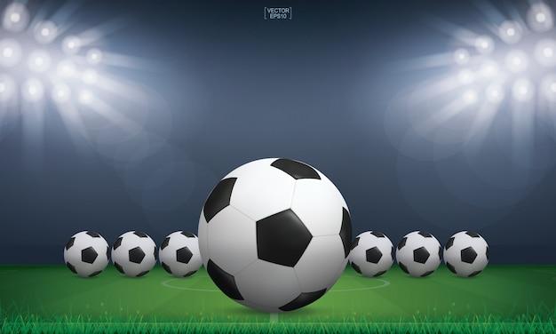 Bola de futebol de futebol e grama verde do fundo do estádio do campo de futebol