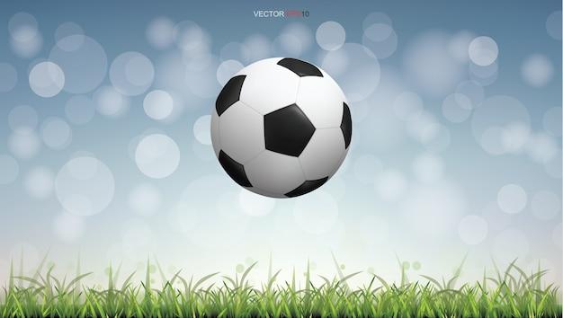 Bola de futebol no campo de grama verde com fundo de bokeh claro
