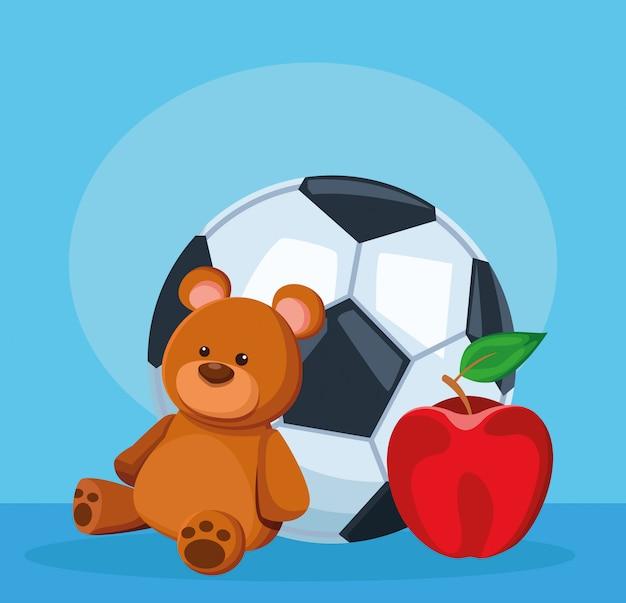 Bola de futebol, urso e maçã frutas sobre azul