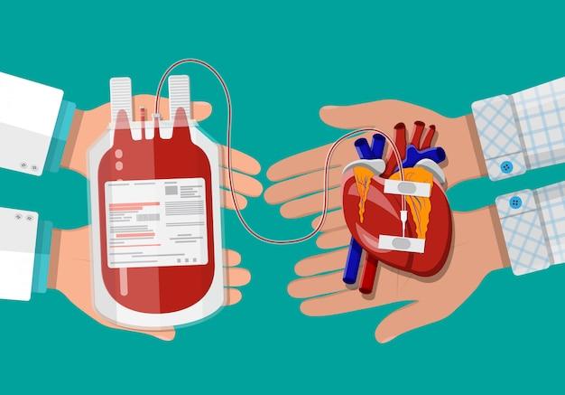 Bolsa de sangue e mão do doador com coração