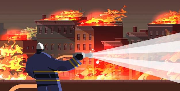 Bombeiro corajoso, extinguindo a chama no bombeiro de casa em chamas em uniforme e capacete, pulverizando água para disparar o retrato de paisagem urbana de conceito de serviço de emergência de combate a incêndios