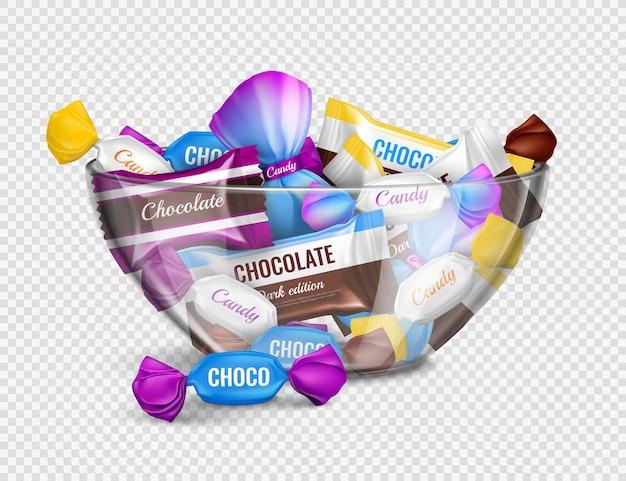 Bombons de chocolate sortidos em invólucros de alumínio na composição de publicidade realista de tigela de vidro contra transparente