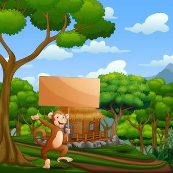 Boneco de um macaco segurando placa de madeira na natureza