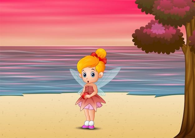 Bonito pequeno amor fada em pé na praia