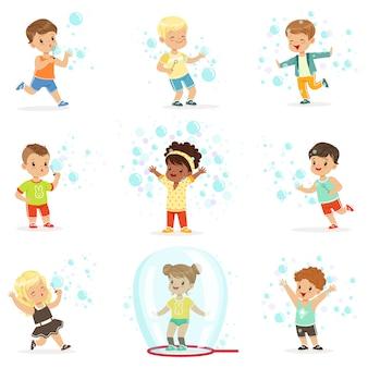 Bonitos meninas e meninos soprando e jogando bolhas de sabão