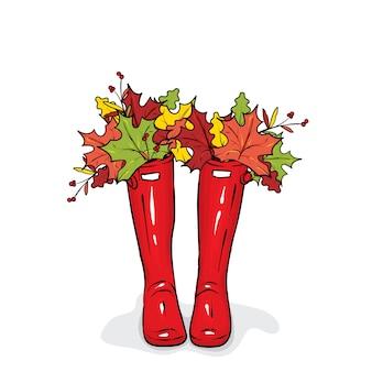 Botas de borracha com folhas de outono coloridas.
