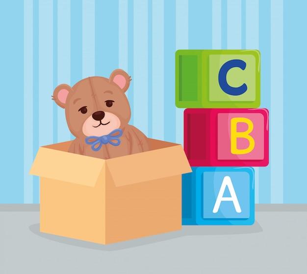 Brinquedos infantis, cubos de alfabeto com ursinho de pelúcia na caixa