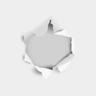 Buraco rasgado e rasgado na folha de papel em um fundo cinza