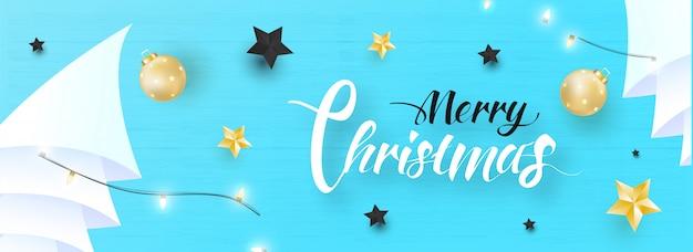 Cabeçalho do site ou banner com texto de caligrafia feliz natal, enfeites, estrelas, árvore de natal de papel origami e guirlanda de iluminação decorada na textura de madeira azul.