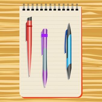 Caderno, caneta vermelha, caneta roxa e caneta azul em uma mesa de madeira