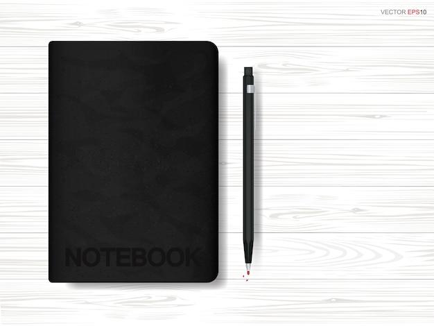 Caderno e lápis em fundo de madeira