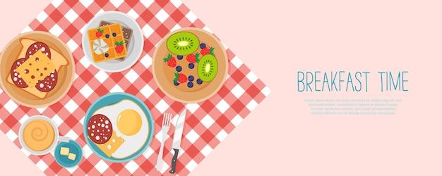 Café da manhã com frutas, bacon e ovos, salsa, torradas com linguiça e queijo.