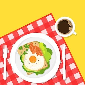 Café da manhã saudável. uma xícara de café e um delicioso sanduíche com abacate, salmão e ovo frito e ervas no fundo de uma toalha de mesa quadriculada.