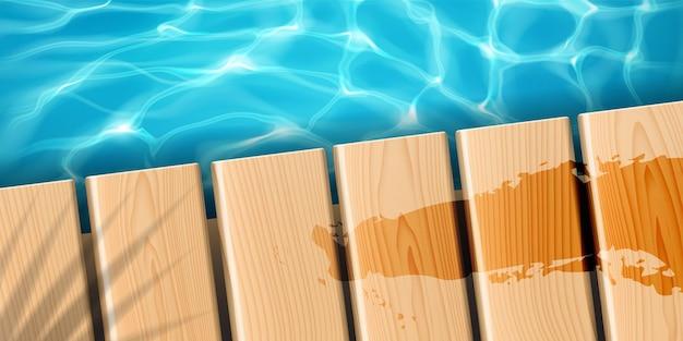 Cais com tábuas de madeira no oceano. doca de madeira do mar com sombra de palmeira e mancha fluida, superfície ondulada da água com reflexo do sol, água limpa e brilhante.