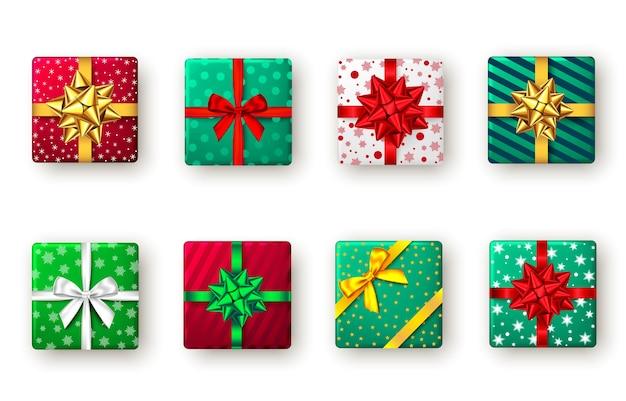 Caixa de presente com fita e laço verdes, vermelhos e dourados.