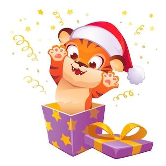 Caixa de presente com um tigre fofo com chapéu de natal salta para fora