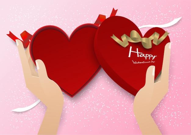 Caixa de presente de coração vermelho aberto de duas mãos com fita vermelha