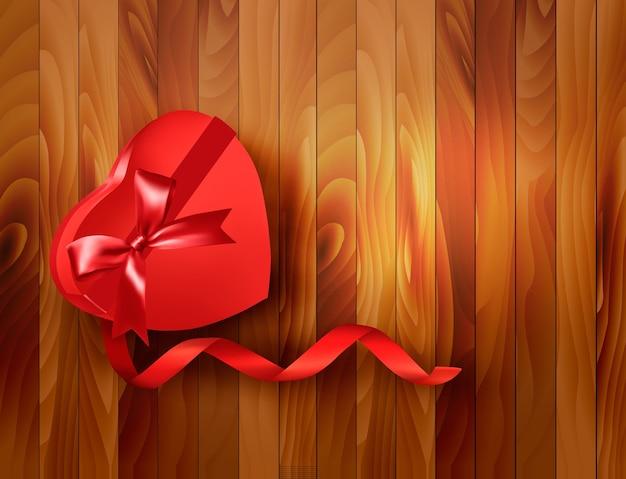 Caixa de presente em forma de coração vermelha com fita em fundo de madeira.