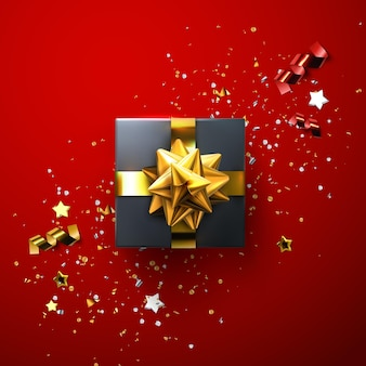Caixa de presente preta com laço dourado brilhante e fitas com confetes cintilantes