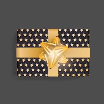 Caixa de presente preta com um padrão de estrelas douradas. laço de fita de ouro.