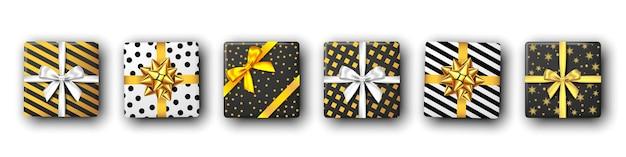 Caixa de presente preto e branco com fita prateada e dourada e vista superior em arco