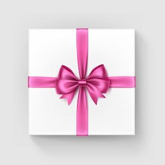 Caixa de presente quadrada branca com luz brilhante brilhante cetim rosa arco e fita vista superior fechar isolado no fundo branco