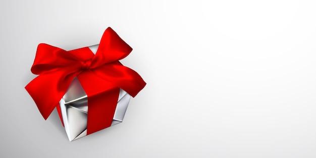 Caixa de presente realista com laço vermelho isolado em fundo cinza