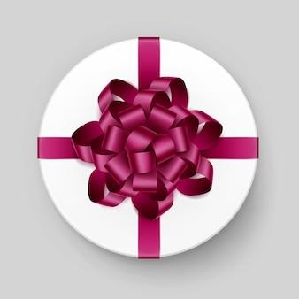 Caixa de presente redonda branca com laço e fita rosa escuro magenta brilhante borgonha vista superior close-up isolado no fundo