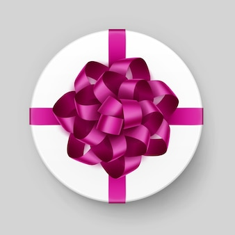 Caixa de presente redonda branca com laço rosa escuro magenta brilhante e vista superior da fita close up isolado no fundo