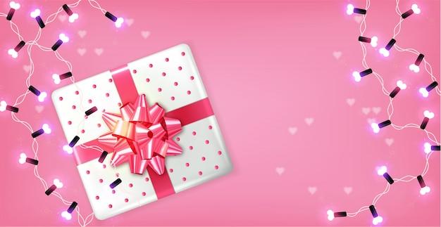 Caixa de presente rosa e guirlanda de luzes