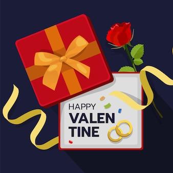 Caixa de presente vermelha aberta com rosa e anel de casamento dentro