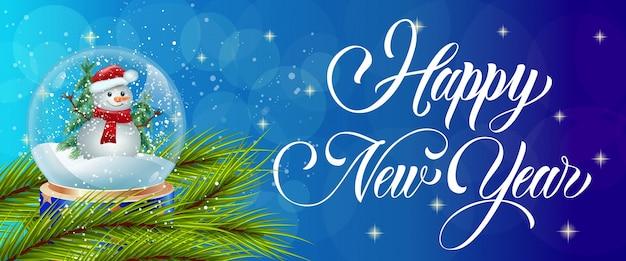 Caligrafia do feliz ano novo com globo de neve