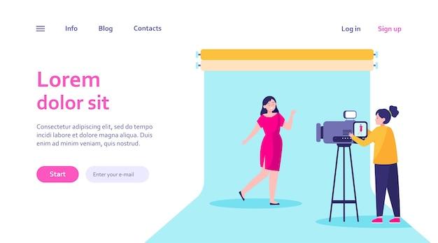 Camerawoman trabalhando com modelo em estúdio. vídeo de filmagem, modelo de web de pano de fundo azul.
