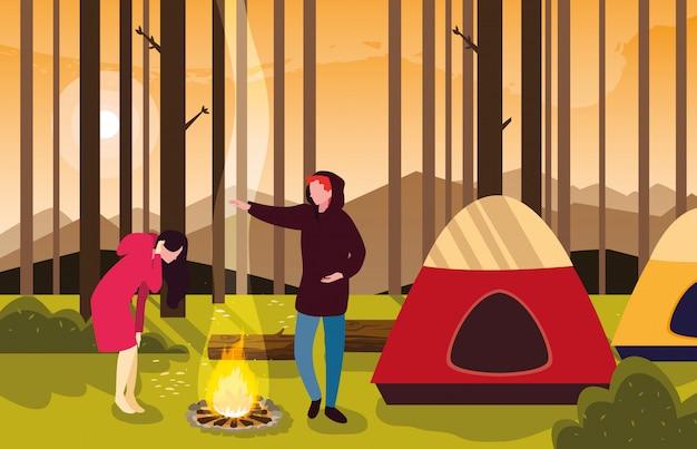 Campistas na zona de acampamento com cena por do sol tenda e fogueira