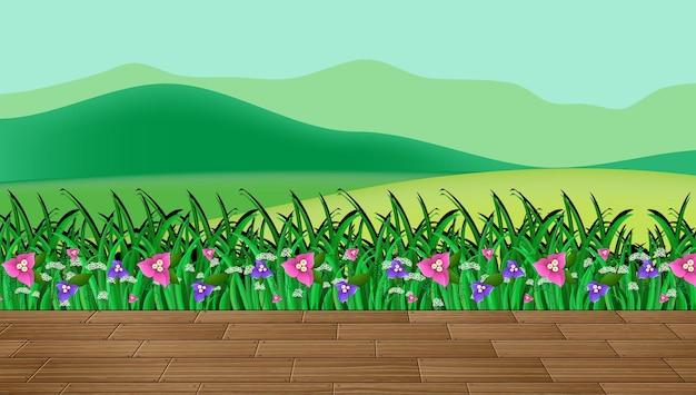 Campo de flores e grama verde com cenário de montanha