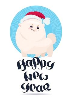 Cão branco de pomerian no chapéu de santa no projeto de rotulação do feriado do cartão do ano novo feliz