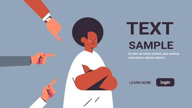 Cara afro-americano deprimido cercado por mãos, dedos zombando, apontando para ele, intimidação, desigualdade, discriminação racial, conceito