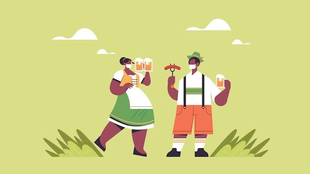 Cara comendo salsicha e bebendo cerveja conceito de festa da oktoberfest homem afro-americano com roupas tradicionais alemãs se divertindo